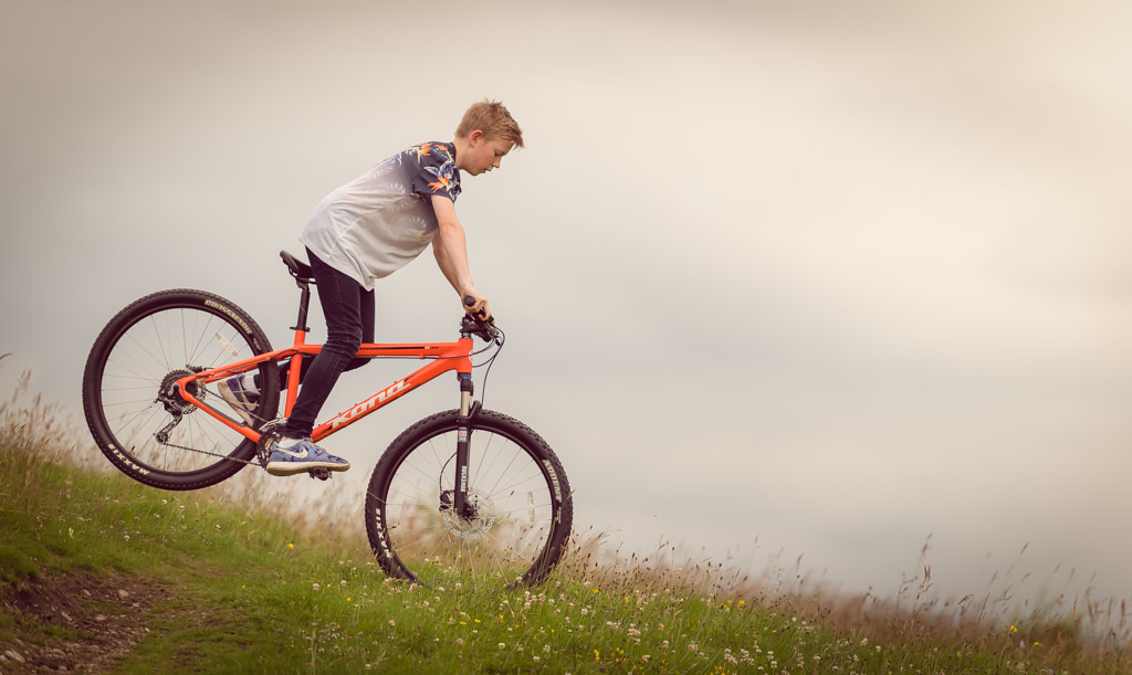 Family photographer Edinburgh - 13 year old boy on mountain bike cycling downhill in a field of flowers
