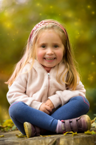 Family photographer Edinburgh - little girl with brown eyes and blonde hair sitting cross legged and smiling