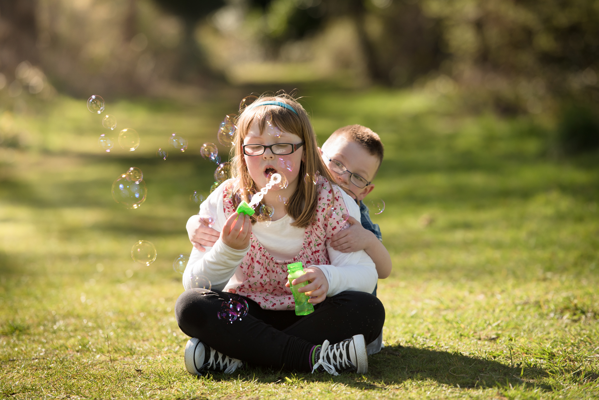 Family photographer Edinburgh - 8 year old girl and 5 year old brother sitting blowing bubbles in the evening sunshine at Lauriston Castle, Edinburgh