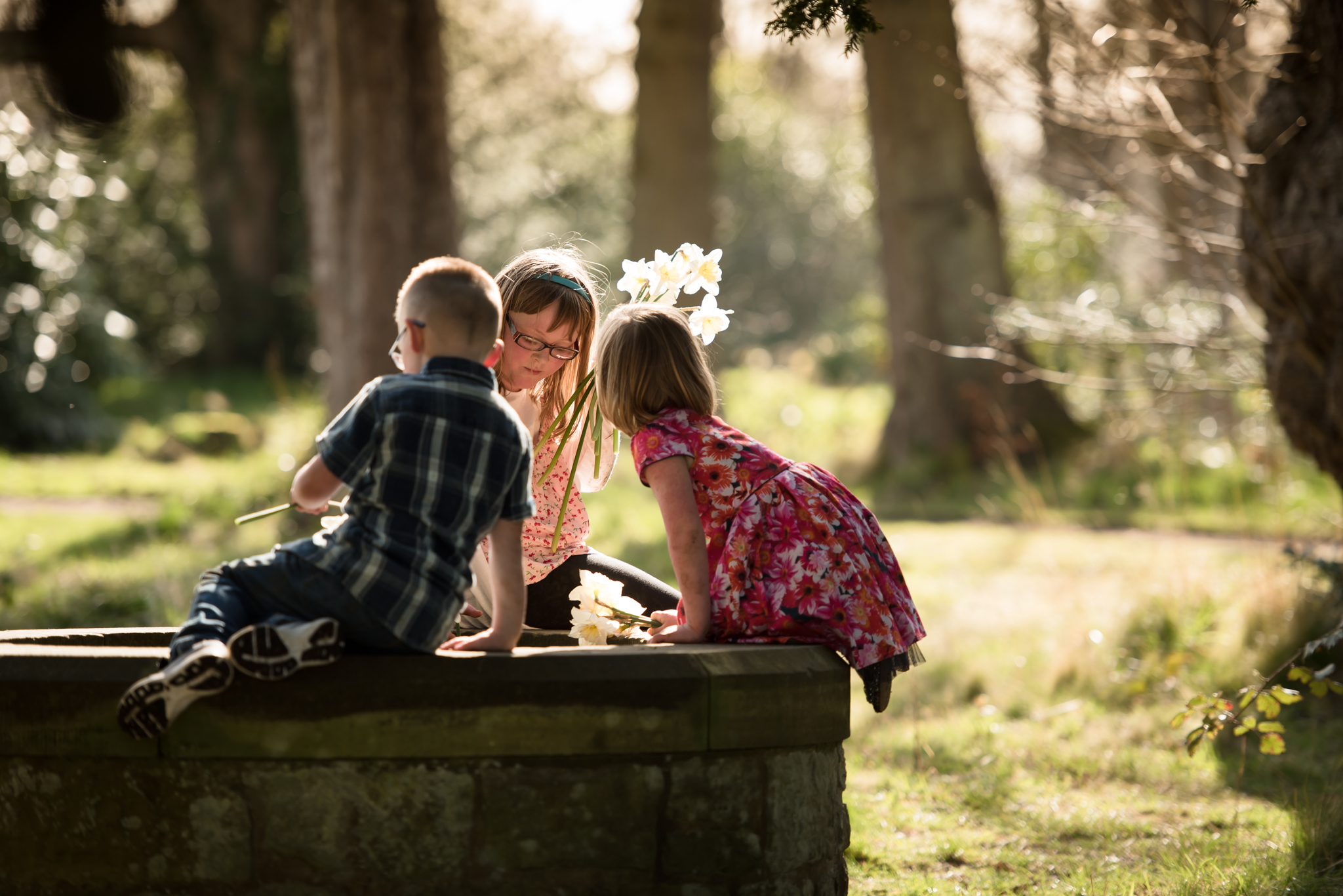 Family photographer Edinburgh - two little girls and little boy sitting on the well at Lauriston Castle in the evening sunshine