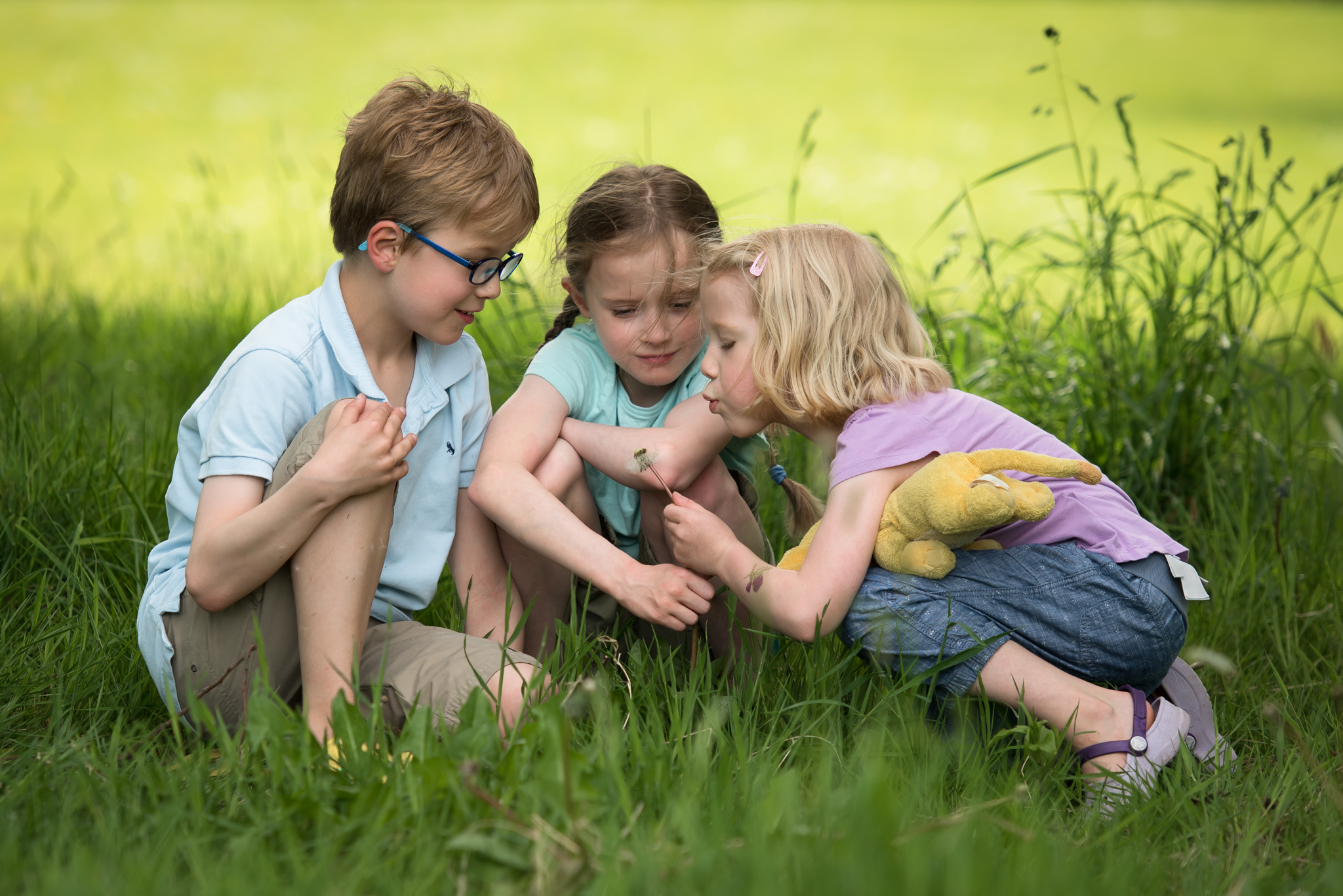 Family photoshoot Edinburgh - three children sitting in grass with dandelion