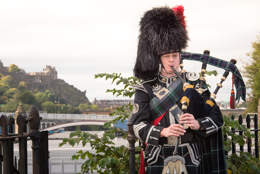 bagpiper photos - Bagpiper in full highland dress playing in front of North Bridge and Edinburgh Castle